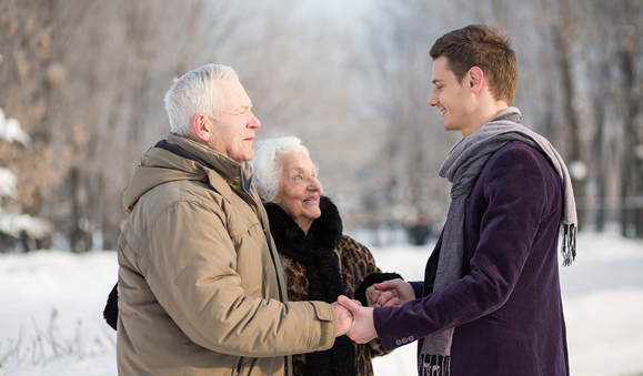 Young man wearing a scarf greets an elderly couple in the park in winter